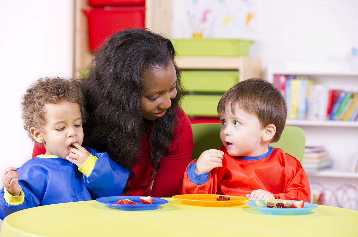 Children eating fruit at a nursery with their carer